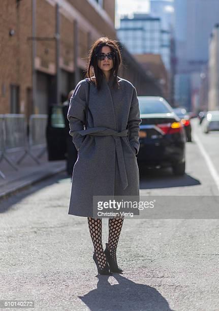 Fashion blogger Lainy Hedaya of Haute Inhabit wearing Prada sunglasses a grey Toteme wool coat Louboutin heels and Proenza Schouler stockings seen...