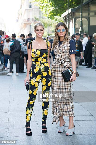Fashion blogger Lala Rudge wears a Dolce Gabbana jumpsuit Chanel clutch bag and Azzedine Alaia shoes with Fashion blogger Thassia Naves who wears a...