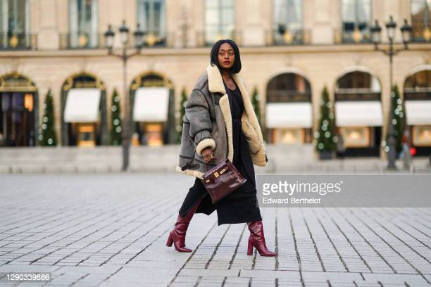 """Fashion blogger Linaose wears a """"bombardier"""" aviator brown/gray jacket with sheep wool inner lining from Acne Studio, a black slit dress from Sancia,..."""