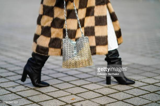 "Fashion blogger Linaose wears a brown and beige checked fluffy faux fur long winter coat ""Nino Check"" from Stand Studio, a metallic silver mesh bag..."