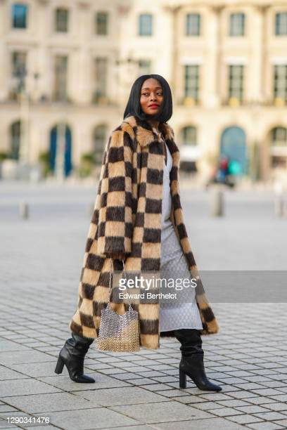 "Fashion blogger Linaose wears a brown and beige checked fluffy faux fur long winter coat ""Nino Check"" from Stand Studio, a white low-neck v-neck..."