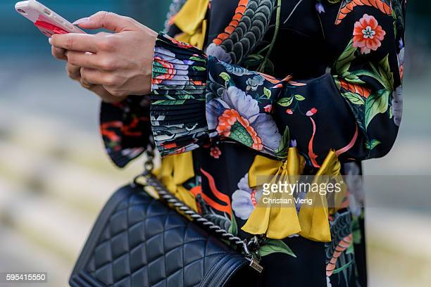 Fashion blogger Lisa Hahnbueck on her phone wearing a Gucci Silk Dress with yellow bows and floral print black Chanel Boy Bag on August 25 2016 in...