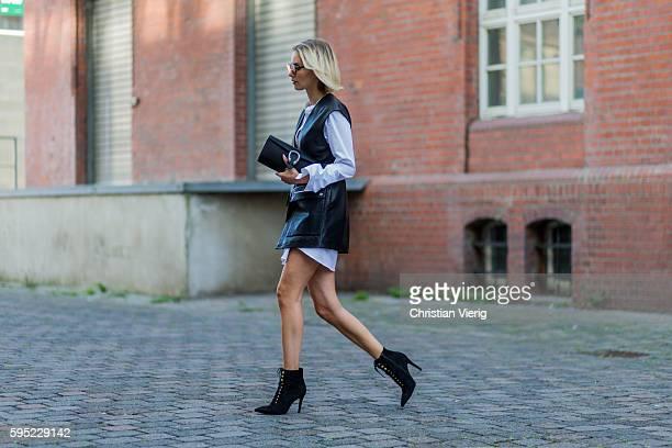 Fashion blogger Lisa Hahnbueck wearing black Set leather vest white Cos Maxi Sleeve black Mai Più Senza ankle boots black Gucci Dionysus Clutch on...