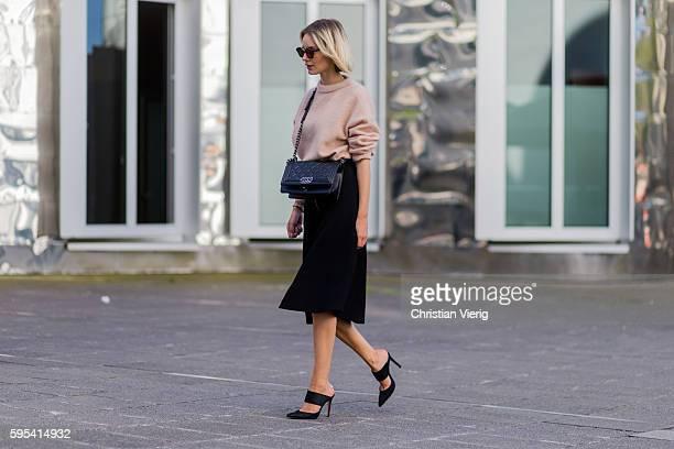 Fashion blogger Lisa Hahnbueck wearing Dior Abstract sunglasses a salmon pink Acne Merino Knit black Set Midi Skirt black Chanel Boy Bag black...