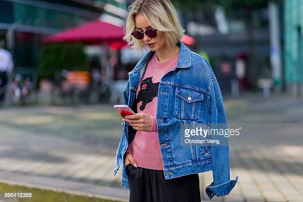 Fashion blogger Lisa Hahnbueck writing a text message on her phone wearing Dior Abstract sunglasses blue denim Balenciaga Jeans jacket a pink Gucci...