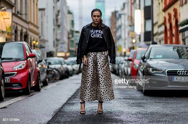 Fashion blogger Lou Beyer wearing a black Tigha leather jacket, a black super girl sweater from Articus Mini, leopard printed culottes from c meo...