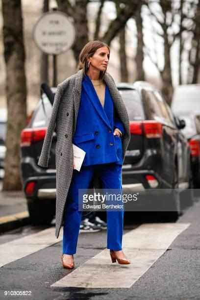 Fashion blogger Loulou de Saison wears a blue suit blazer jacket a gray coat heels shoes outside Maison Rabih Kayrouz during Paris Fashion Week Haute...