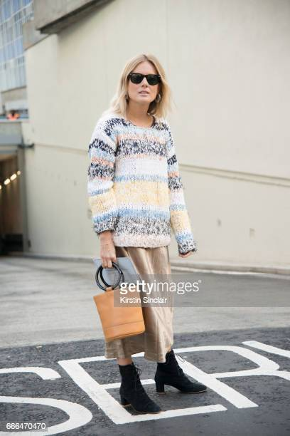 Fashion blogger Lucy Williams wears a Chloe jumper Vince skirt By Far boots Simon Miller bag and RayBan sunglasses on day 4 of London Womens Fashion...