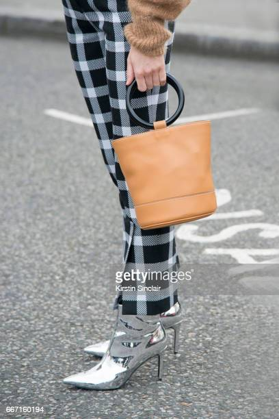 Fashion blogger Lucy Williams wears Christopher Kane trousers Other Stories sweater Topshop boots Simon Muller bag on day 4 of London Womens Fashion...