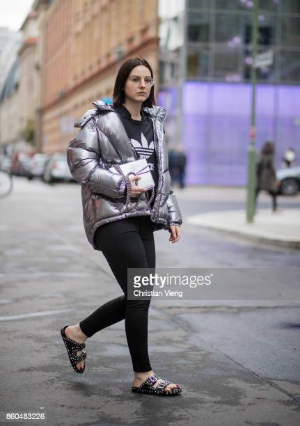 Fashion blogger Maria Barteczko wearing a metallic quilted down jacket Topshop cropped logo shirt Adidas black shiny jeans Mango studded leather...