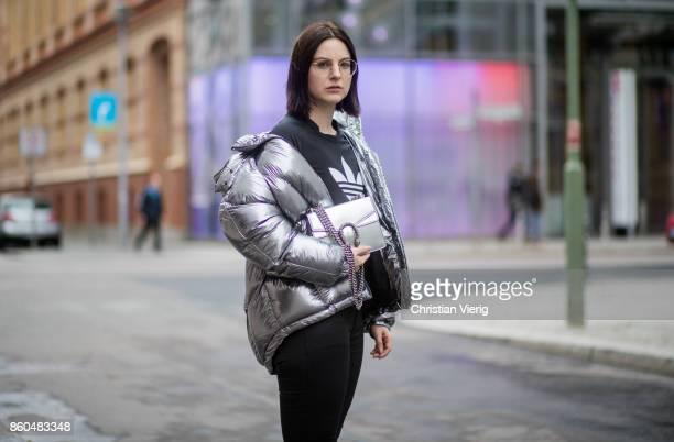 Fashion blogger Maria Barteczko wearing a metallic quilted down jacket Topshop cropped logo shirt Adidas black shiny jeans Mango studded leather...