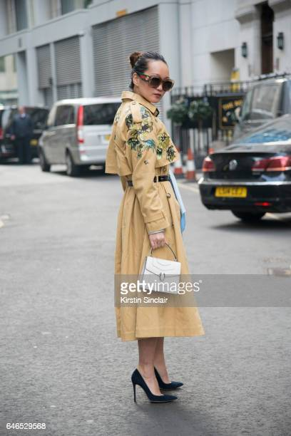 Fashion blogger Mariko Kuo wears a River Island Studios coat and dress Bvlgari bag Gucci sunglasses and Gianvito Rossi shoes on day 2 of London...
