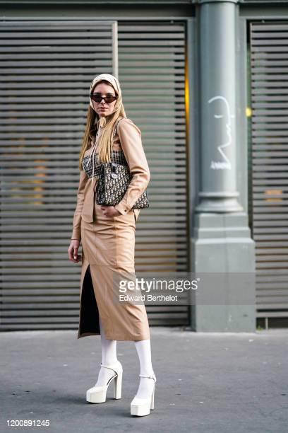 "Fashion blogger ""Mascarada Paris"" wears a beige Christian Dior headscarf, sunglasses, a camel-color leather side-split dress, a matched jacket, a..."