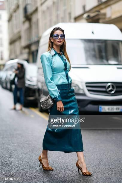 "Fashion blogger ""Mascarada Paris"" wears sunglasses, a blue pvc shirt, a blue turquoise shiny skirt, a silver metallic bag, leopard print shoes,..."