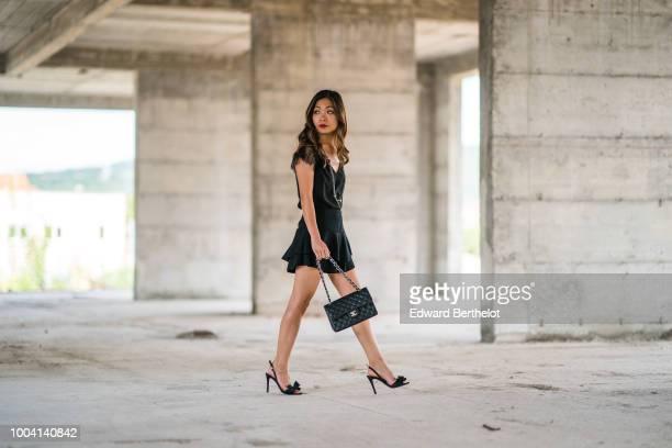 Fashion blogger Maymaryb wears a black pleated lace dress a black Chanel bag Charles Jourdan heels shoes during Feeric Fashion Week 2018 on July 22...