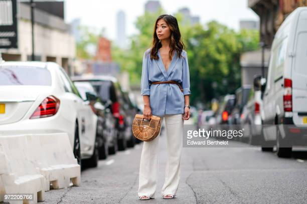Fashion blogger Maymaryb wears a blue blazer jacket a brown leather belt a brown Cult Gaia ark small bamboo clutch white flared pants sandals during...