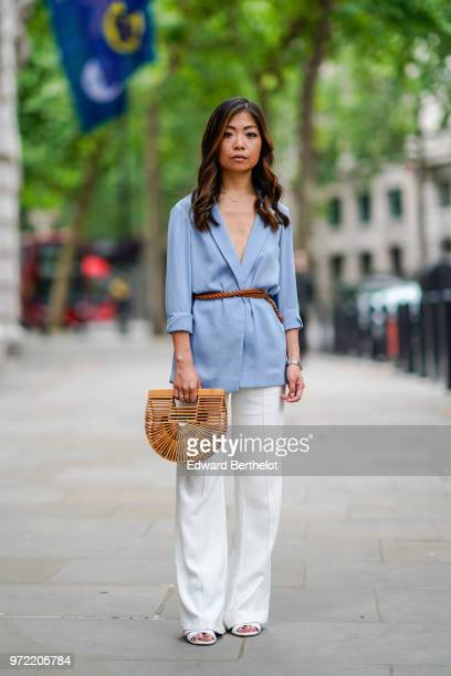 Fashion blogger Maymaryb wears a blue blazer jacket, a brown leather belt, a brown Cult Gaia ark small bamboo clutch, white flared pants, sandals,...