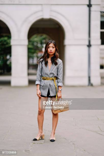 Fashion blogger Maymaryb wears a gray blazer jacket, a yellow Off-White belt, a black skirt, a Chanel bag, Chanel slingback shoes, during London...