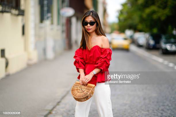 Fashion blogger Maymaryb wears a red offshoulder ruffled top a Cult Gaia bag white flared pants during Feeric Fashion Week 2018 on July 20 2018 in...