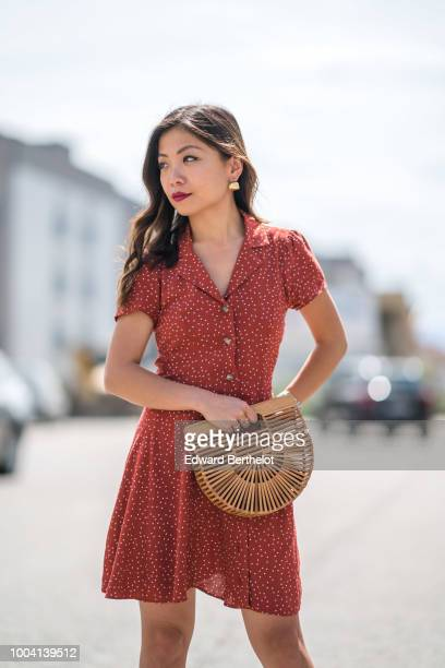 Fashion blogger Maymaryb wears a red pleated dress with white printed dots a Cult Gaia wooden bag earrings during Feeric Fashion Week 2018 on July 22...