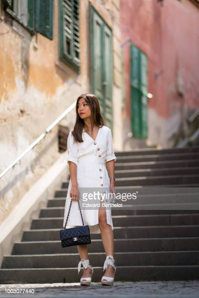 Fashion blogger Maymaryb wears a white dress a black Chanel bag wedges shoes during Feeric Fashion Week 2018 on July 21 2018 in Sibiu Romania