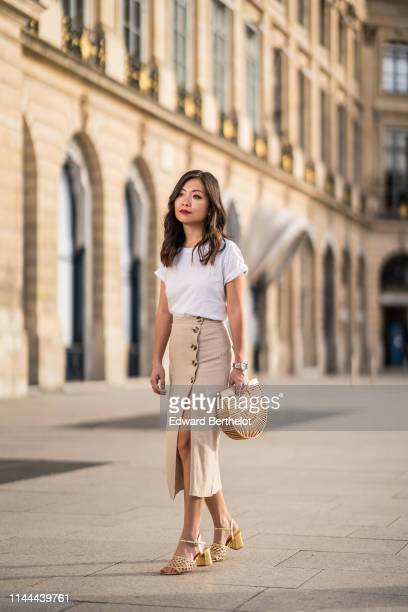 Fashion blogger Maymaryb wears a white tshirt a beige opened skirt with buttons a Cult Gaia wooden bag golden shoes on April 22 2019 in Paris France