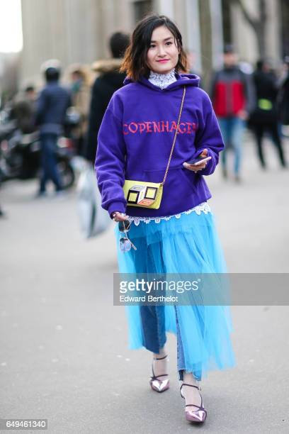 Fashion blogger Miu wears a Copenhagen purple hoodie sweater a yellow bag a blue skirt and pink shoes outside the Miu Miu show during Paris Fashion...