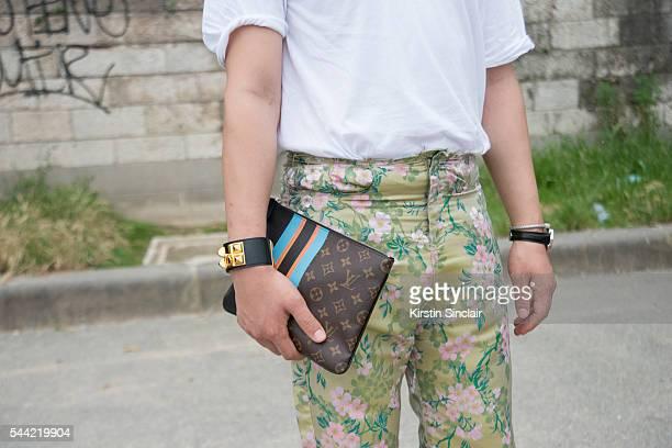 Fashion Blogger Moki Cho wears a Faith Connexion shirt Marques Almeida trousers Loewe bracelet and a Louis Vuitton clutch on day 1 of Paris...