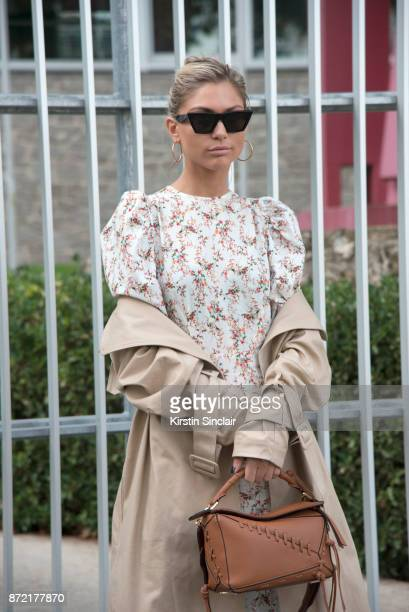 Fashion blogger Natalia Georgala wears a Nam dress HM coat Celine sunglasses and a Loewe bag day 4 of Paris Womens Fashion Week Spring/Summer 2018 on...