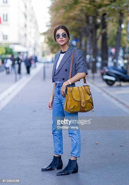 Fashion blogger Negin Mirsalehi wearing a Chloe Lexa bag and denim jeans and a plaid jacket on October 3 2016 in Paris France