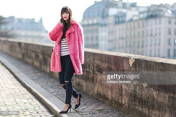 Fashion blogger Nikita Wong wears a Manoush pink coat a Saint Laurent bag an IKKS top Zara jeans and Manoush shoes during a street style session on...