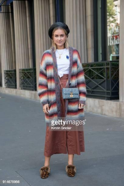 Fashion blogger Nina Suess wears a Dior bag and hat Chloe cardigan Tibi trousers and Christian Louboutin shoes day 5 of Paris Womens Fashion Week...