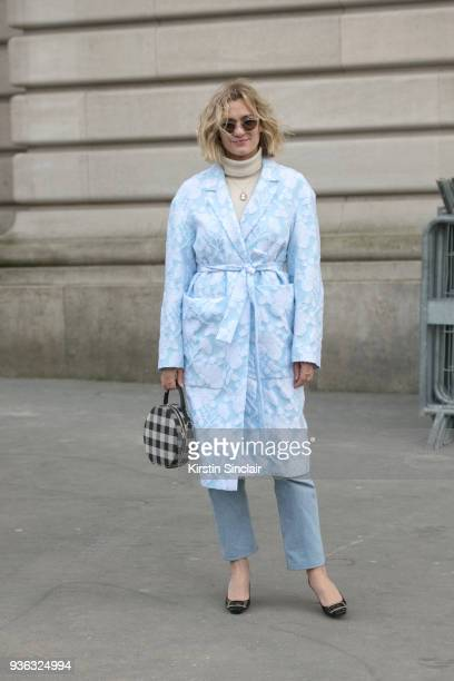 Fashion blogger of adenorah AnneLaure Mais wears a Rochas coat Roger Vivier shoes and vintage jeans and sunglasses day 3 of Paris Womens Fashion Week...