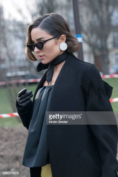 Fashion blogger Olivia Culpo wears Le Specs sunglasses Andres Gallardo earrings Rochas top and coat day 3 of Paris Womens Fashion Week Spring/Summer...
