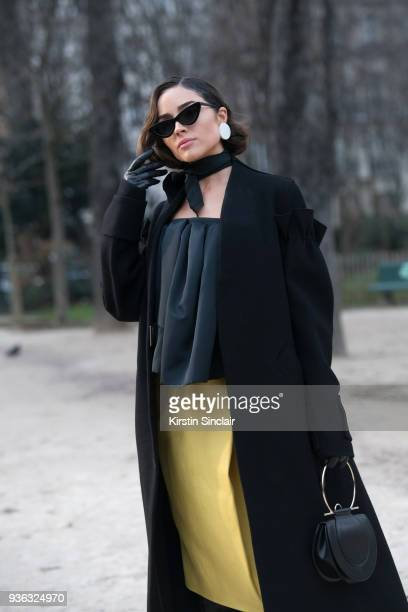 Fashion blogger Olivia Culpo wears Le Specs sunglasses Salvatore Ferragamo bag Andres Gallardo earrings Rochas top skirt and coat day 3 of Paris...