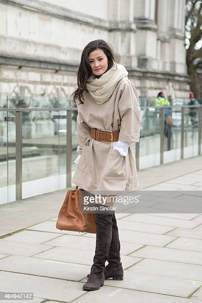Fashion blogger Peony Lim wears an Isabel Marant scarf her own dress and a Hermes belt and bag on February 24 2015 in London England
