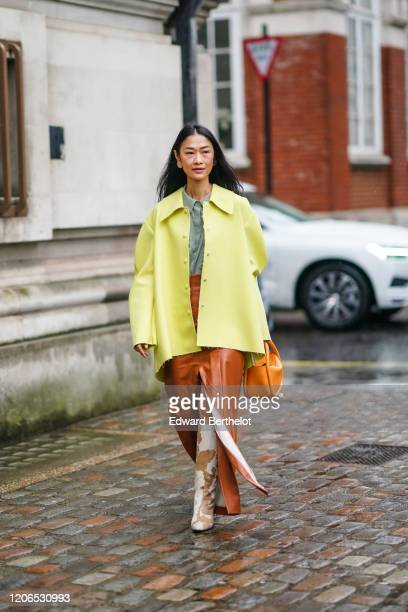 Fashion blogger Pornwika wears a yellow oversized jacket, an orange bag, a brown leather skirt, a green shirt, yellow and pale brown cow pattern...