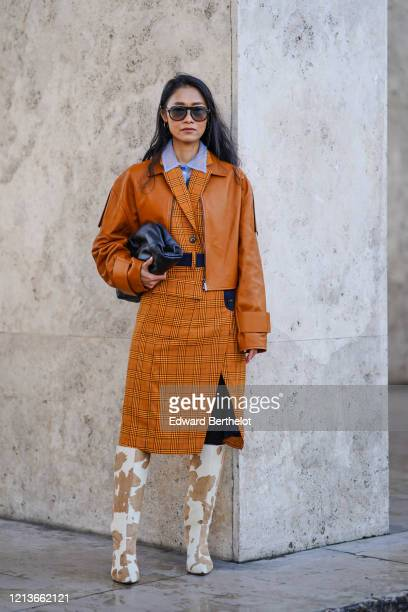 Fashion blogger Pornwika wears sunglasses, a mauve shirt, an orange/brown leather jacket, a checked dress, cow pattern printed white and brown high...