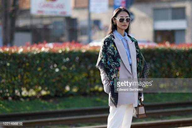 Fashion blogger Pornwika wears sunglasses, earrings, a Gucci floral print scarf over the shoulders, a blue mesh shirt, a gray oversized blazer...