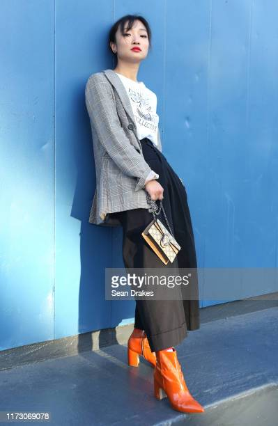 Fashion blogger Qianwen Chen of San Francisco punctuates her look with pumpkin-colored ankle boots during New York Fashion Week at Pier 59 Studios on...