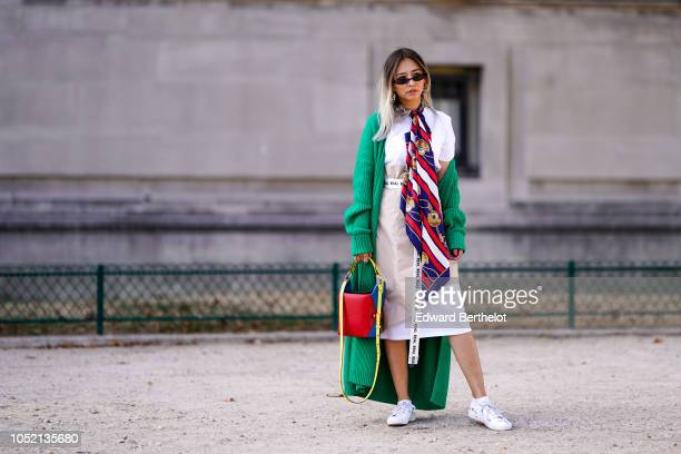 Fashion blogger Queen Horsfall wears sunglasses a white tshirt a beige skirt a 'Real' long belt from Belt Dept a Jeff Wan blue and red bag sneakers a...