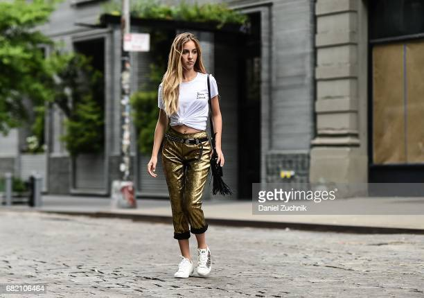 Fashion Blogger Rosa Crespo is seen in Noho wearing an Iorane World tshirt Nude gold pants Ash sneakers and Salar Milano bag on May 11 2017 in New...