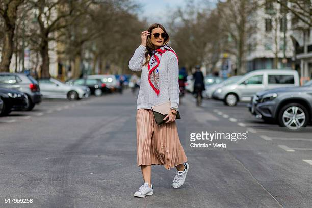 Fashion blogger Sofia Grau is wearing a salmon pink skirt from Zara white sneakers from Adidas a grey sweater from Mango a pink black clutch from...