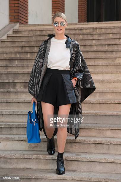Fashion Blogger Sofie Valkiers is wearing a Roberto Cavalli cape Acne top Pinko skirt What For boots and Christian Dior sunglasses on day 6 of Paris...