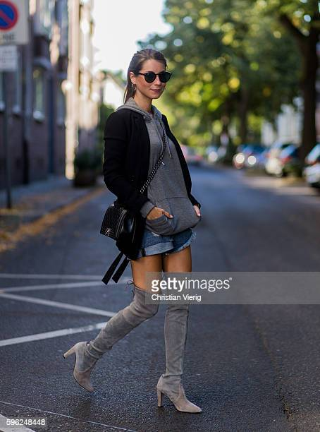 Fashion blogger Stephanie van Klev wearing black Ray Ban sunglasses a black blazer from Zara a grey hoody from Monki blue ripped denim jeans shorts...