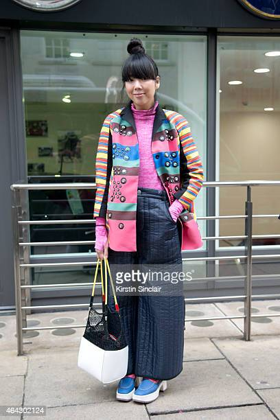Fashion blogger Susie Lau wears a Peter Pilotto coat Craig Green trousers Marc Jacobs shoes and Toga bag on February 23 2015 in London England