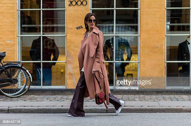 Fashion blogger Sylvia Haghjoo wearing Chloe Hudson bag, Adidas sneaker, Celine earrings and sunglasses, By Malene Birger pants, top and coat during...