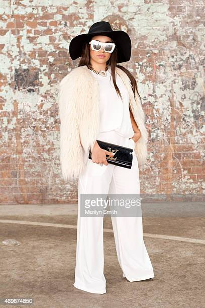 Fashion Blogger Tammy Christina wears Pasduchas trousers and top Lack of Color hat Le Spec sunglasses and a Louis Vuitton bag at MercedesBenz Fashion...
