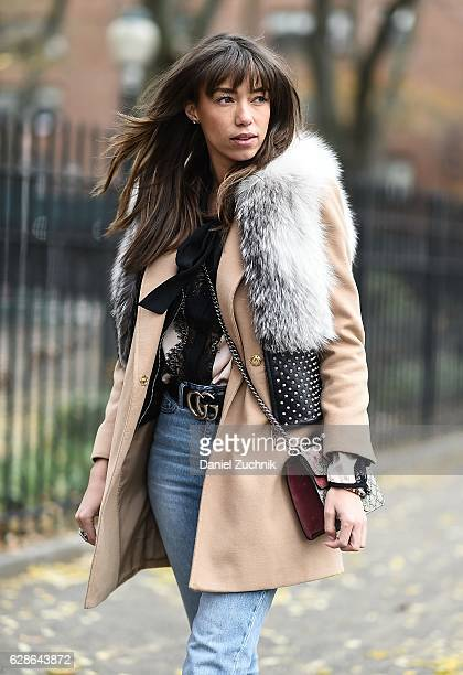 Fashion Blogger Thania Peck is seen wearing a Thomas Wylde fur vest Top Shop coat Cheap Monday denim pants Gucci belt and purse on the streets of the...