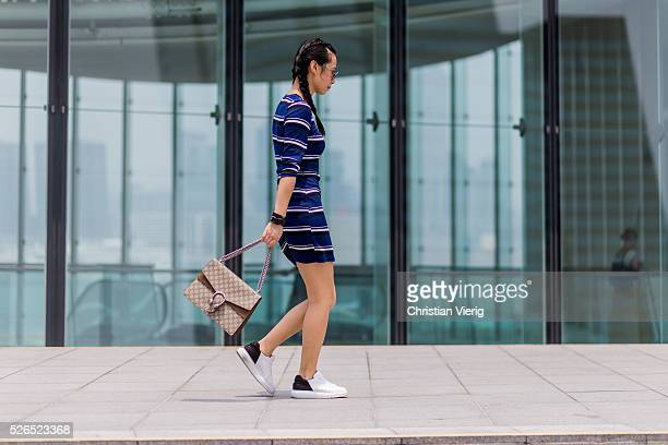 Fashion blogger Theresa Twee Wu with braids wearing a navy black white striped HM dress a Gucci Dionysus shoulder bag and white Pedder Red sneakers...